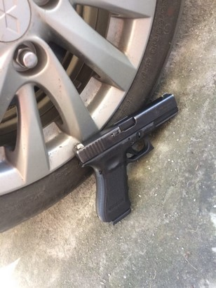 glock 17 besides a car wheel side view on the floor