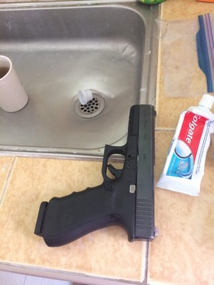 glock 17 g4 and magazine on kitchen sink beside toothpaste side view