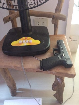glock 17 g4 and magazine on top of wooden chair beside electric fan side view