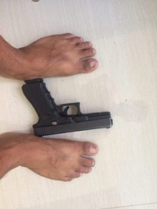 glock 17 on the floor in between mans feet side view